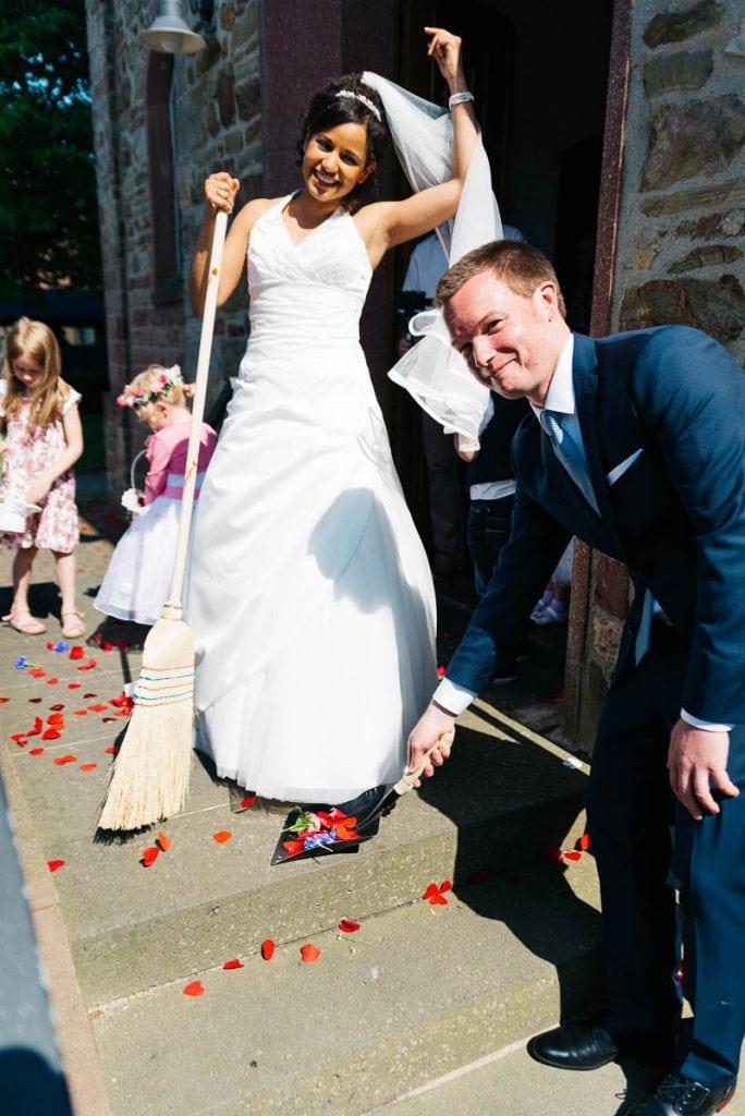 Das Brautpaar kehrt das Konfetti weg.