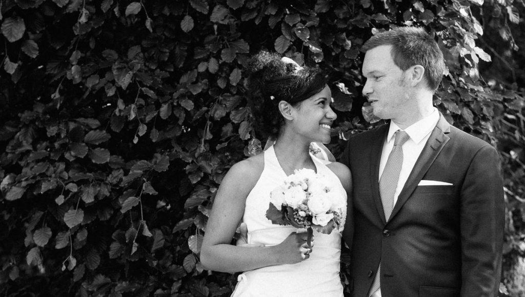 Das Brautpaar vor einer Hecke.