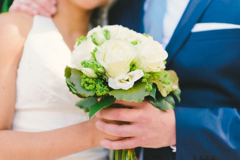 Braut und Bräutigam halten den Brautstrauß.