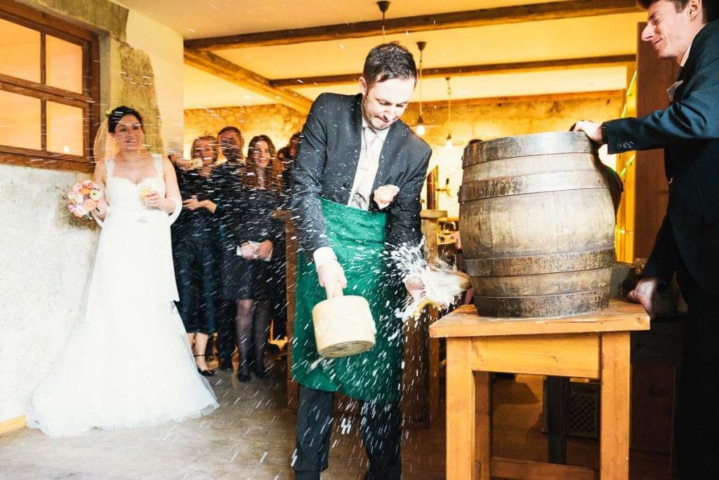 Der Bräutigam stößt ein Bierfass an.