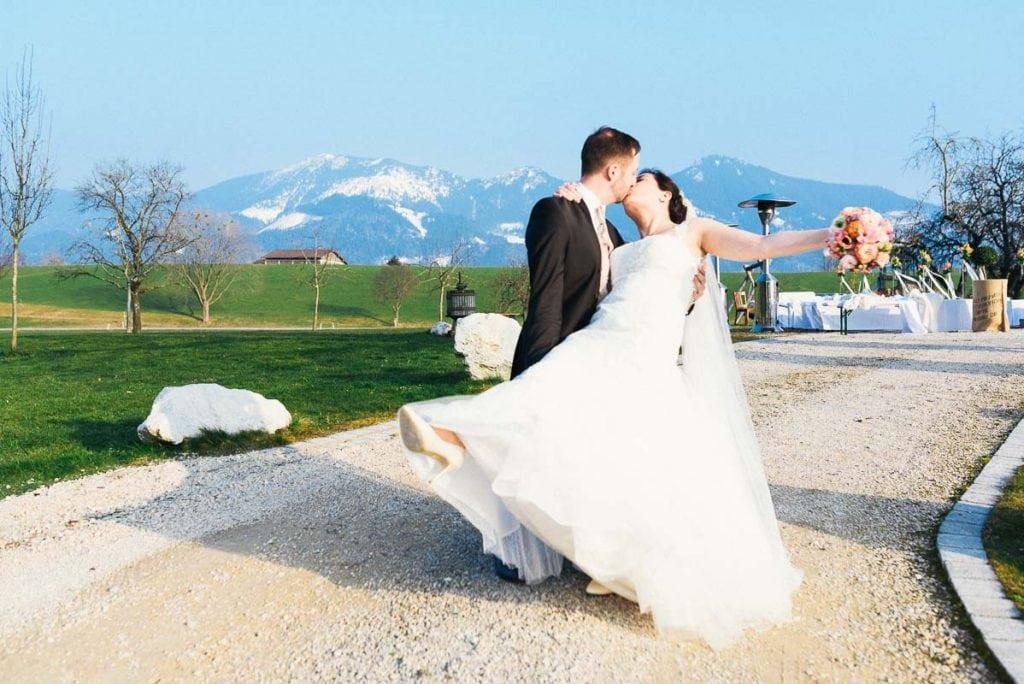 Das Brautpaar küsst sich vor den Alpen.