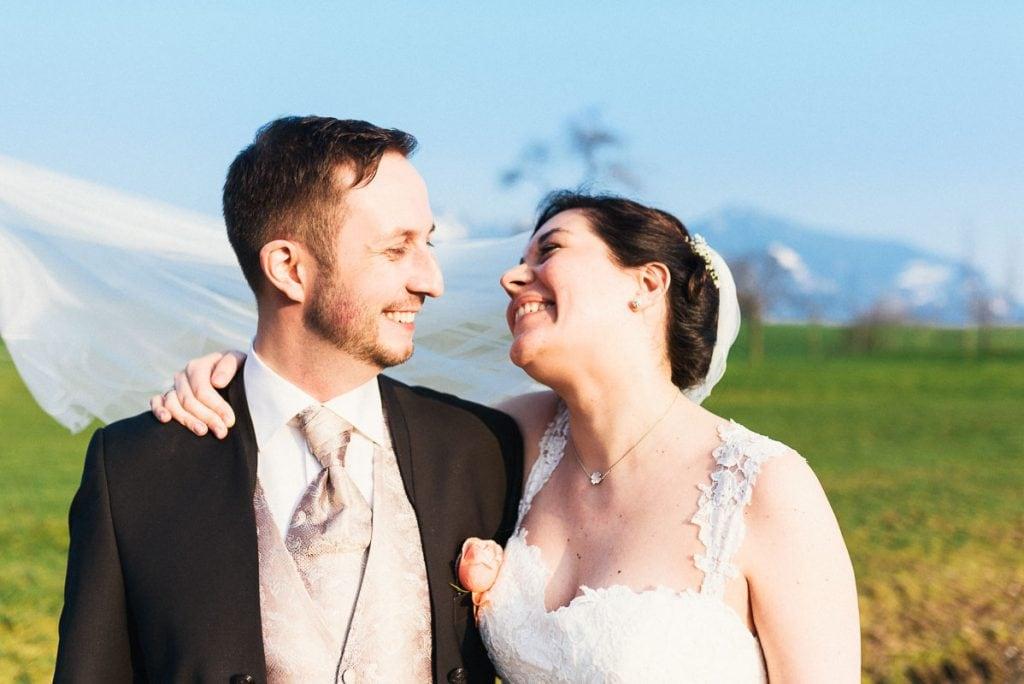 Das Brautpaar lacht sich an.
