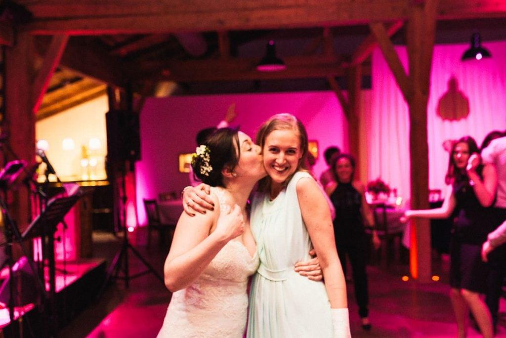 Die Braut küsst einen Hochzeitsgast.
