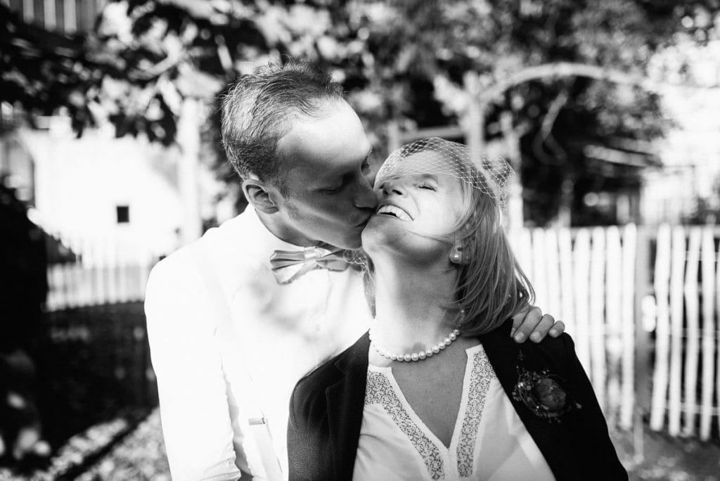 Der Bräutigam küsst die lachende Braut.
