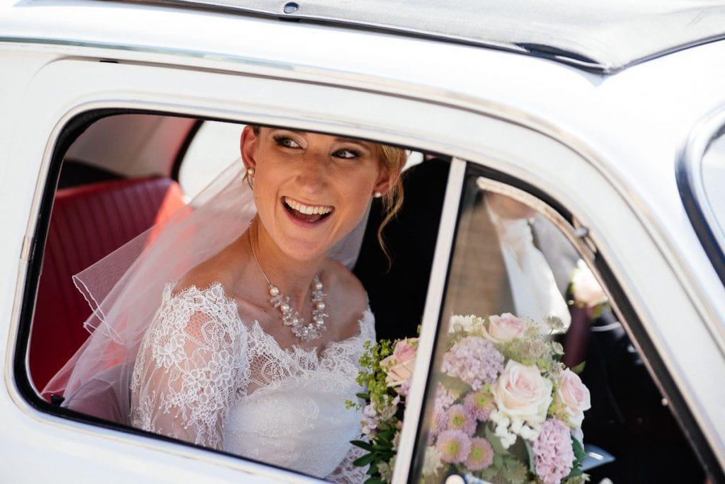 Die Braut schaut durchs Autofenster.