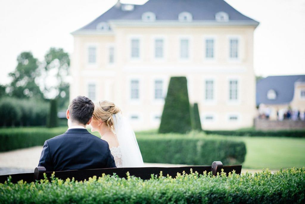 Das Brautpaar auf einer Bank mit dem Schloss im Hintergrund.