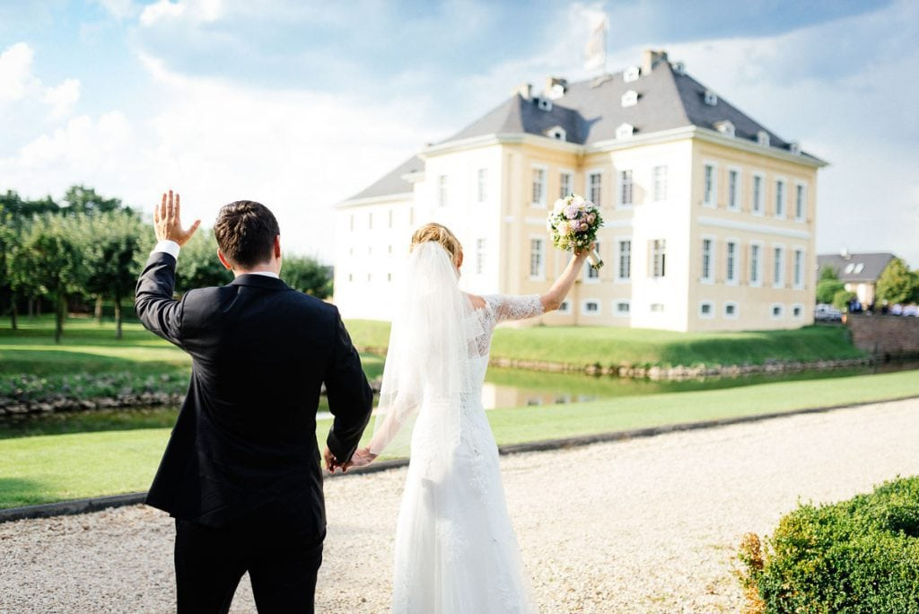 Das Brautpaar winkt den Gästen Am Schloss Miel.