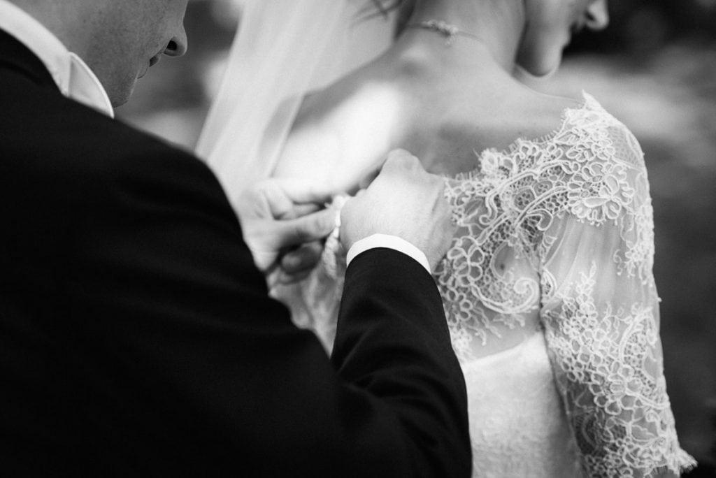 Der Bräutigam schließt das Kleid der Braut.