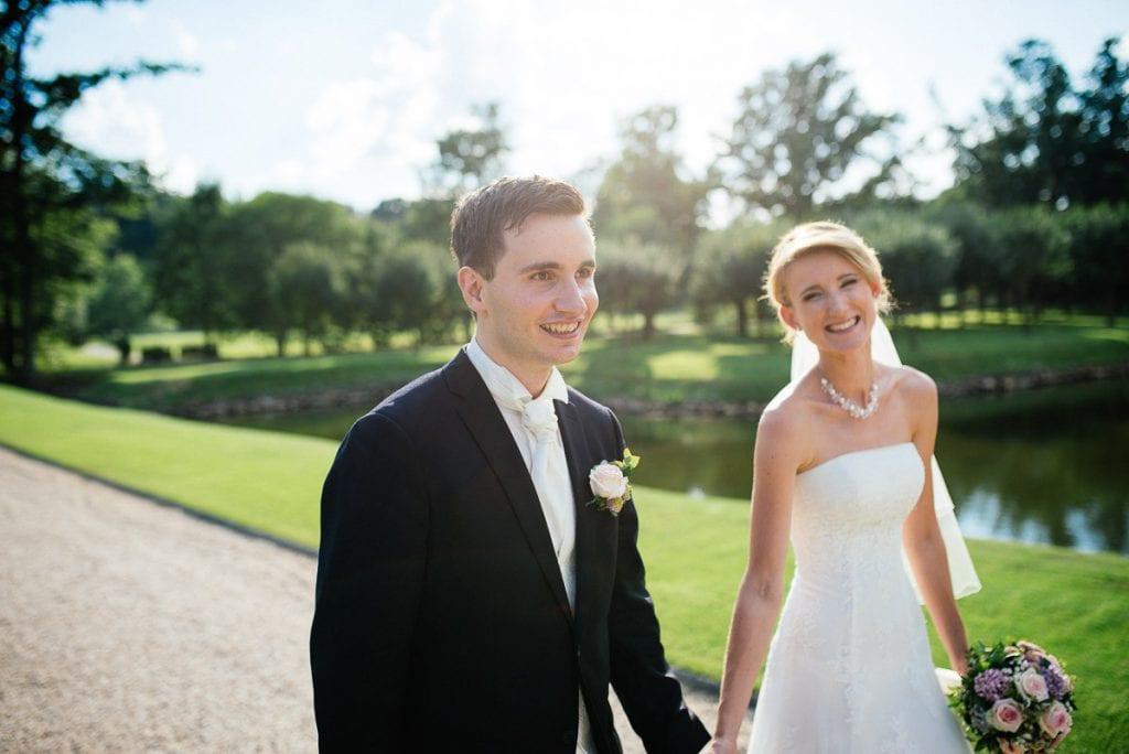Braut und Bräutigam spazieren im Schlosspark.