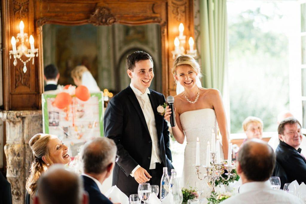 Das Brautpaar hält eine Rede am Tisch.